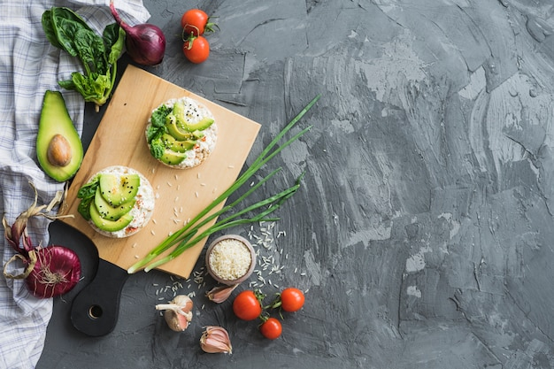 Rice cake with slices of avocado over chopping board with raw ingredients on cement counter