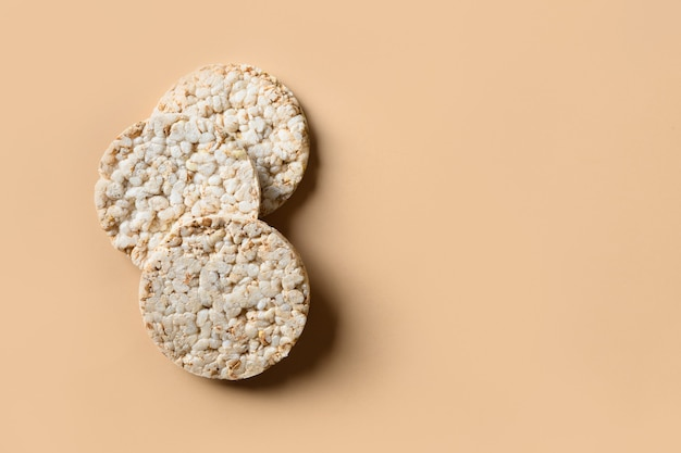 Rice cakes on beige background with copy space.