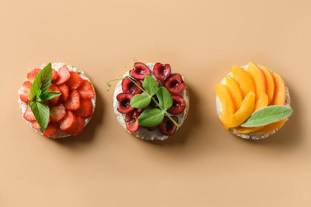 ライス ケーキは、ベージュの背景に果物や果実を飾る健康的なカラフルなビーガン フード