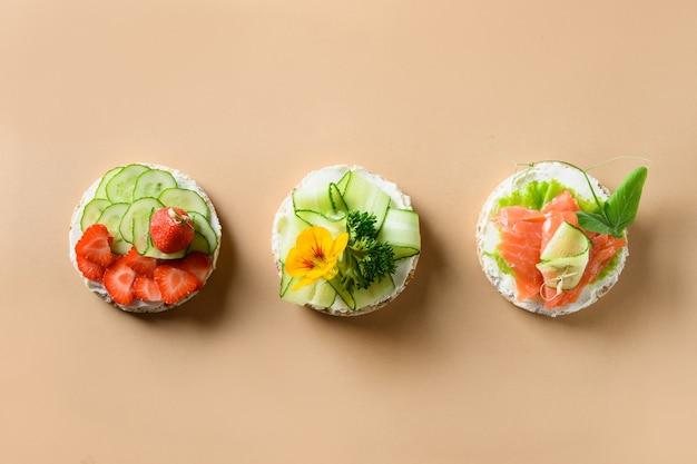 다양한 종류의 떡은 자연 베이지 색 배경에 과일, 야채, 마이크로 그린을 장식합니다.