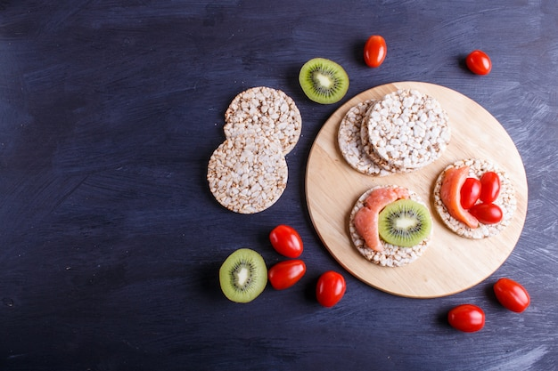 Rice cakes with salmon, kiwi and cherry tomatoes on dark wooden background.