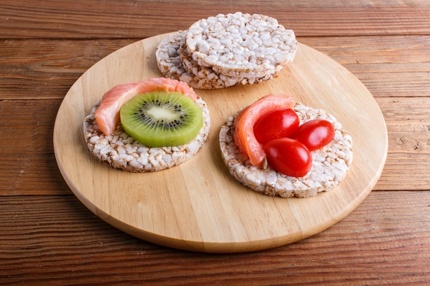 Rice cakes with salmon, kiwi and cherry tomatoes on wood