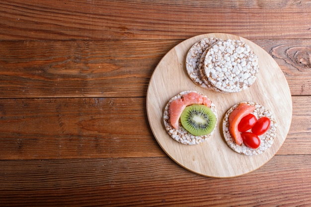 Rice cakes with salmon, kiwi and cherry tomatoes on wooden background.