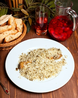 Rice chicken plov with herbs in white plate and composto