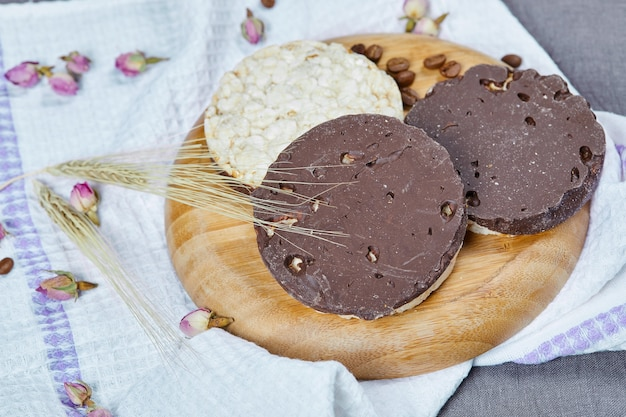 Rice and chocolate crackers on a wooden plate with a tablecloth.