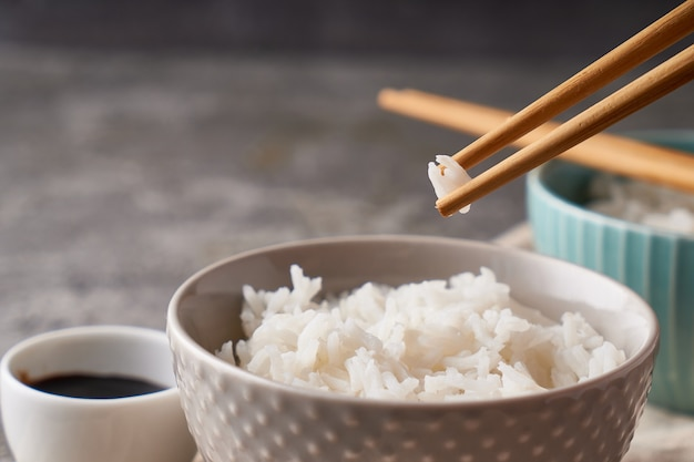 Rice chopsticks, over a bowl of white rice, soy sauce on a dark gray background copy space