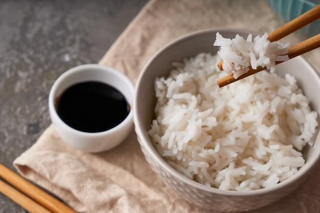 Рисовые палочки для еды, над миской белого риса, соевый соус на темно-сером фоне копирование пространства