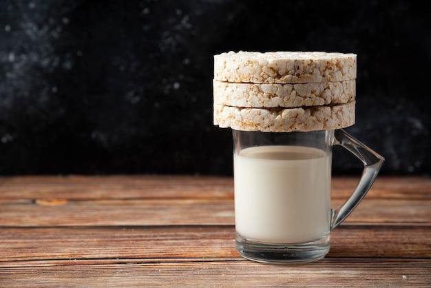 ライスクラッカーと木製のテーブルの上の牛乳のガラス。