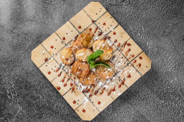 灰色の表面の正方形の木の板にミントを添えたメープルシロップと粉砂糖のライスクラッカー。ビスケットの揚げ物。