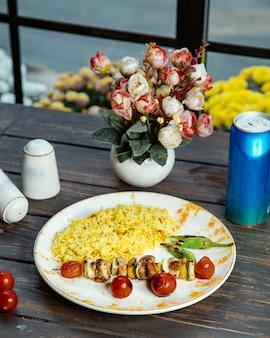 Piatto di riso con spiedino di zucchine e pomodori alla griglia con peperoncino di pollo