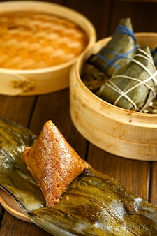Rice dumplings zongzi and bamboo steamer on wooden table