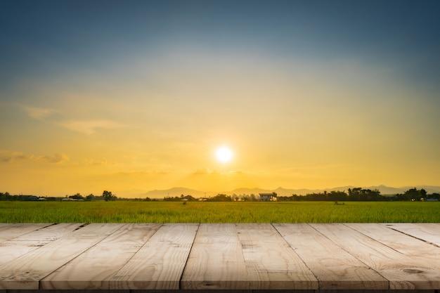 製品の展示とモンタージュのための田んぼの夕日と空の木製テーブル。