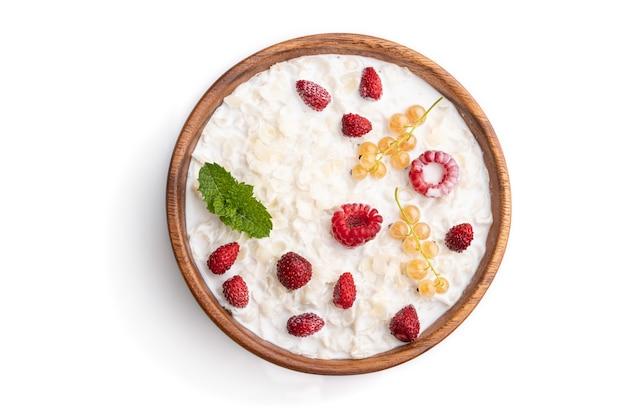 白い背景で隔離の木製のボウルにミルクとイチゴとライスフレークのお粥。上面図、フラットレイ、クローズアップ。