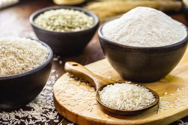 Рисовая мука в глиняном горшочке и деревянной ложкой в деревенском стиле, безглютеновая альтернативная мука и более полезная для здоровья