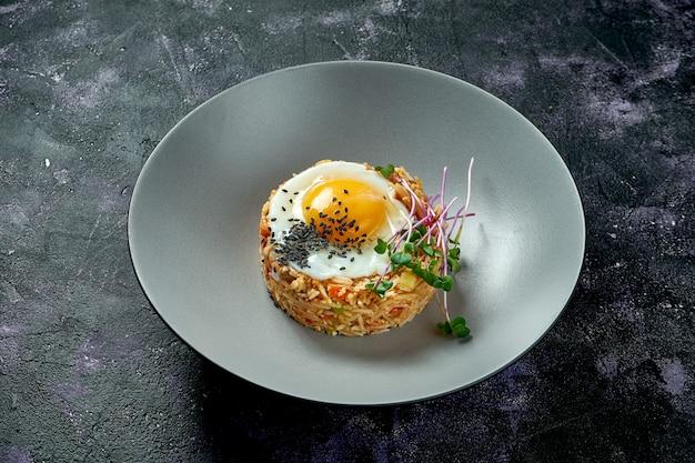 黒い表面に灰色の皿に鶏肉と目玉焼きを鍋で炒めたご飯。アジアの屋台