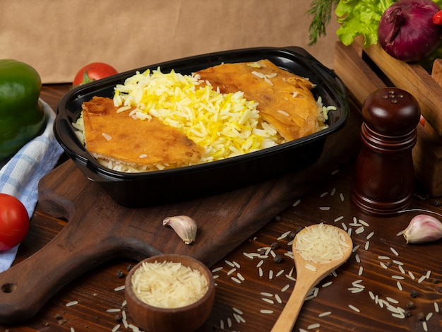 Rice garnish, plov takeaway in black container on wooden board