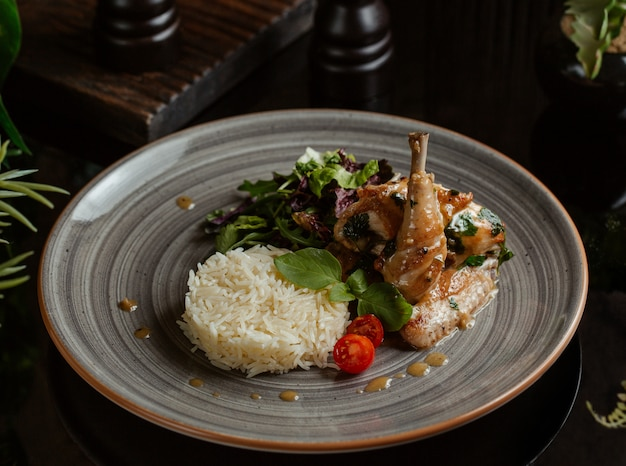 Rice garnish with spicy grilled chicken leg in a granite plate