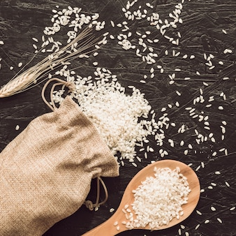 Rice grains on sack with wooden spoon