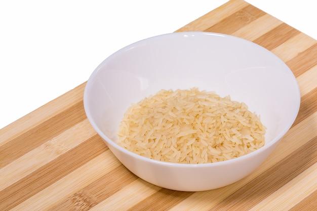 흰 벽에 나무 보드에 흰색 그릇에 쌀 밀가루.