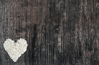Rice heart shape made on wooden black backdrop