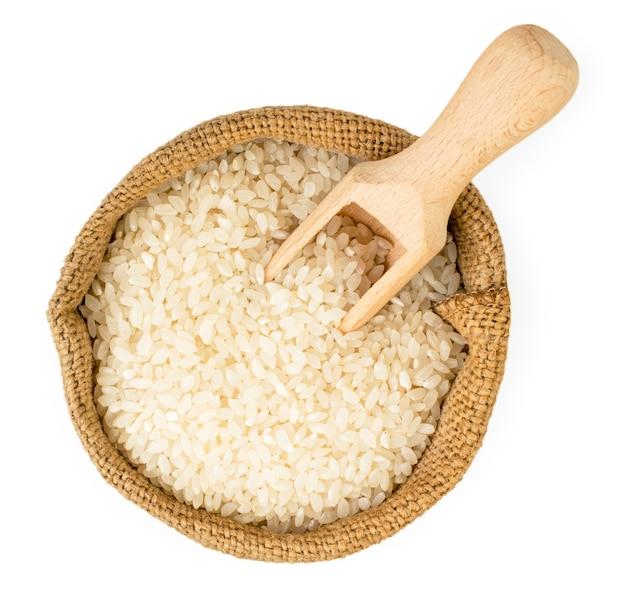 袋に入ったご飯と白い背景の上の木のスプーン