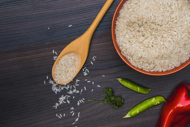Рис в миску, овощи и деревянной ложкой на коричневой деревянной поверхности