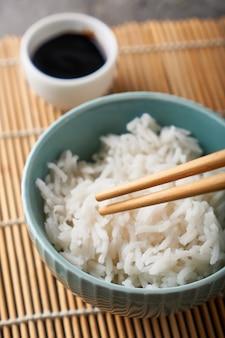 磁器のボウルにご飯、箸、醤油、灰色の石のテーブルで提供クローズアップ