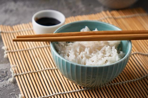 Рис в фарфоровой миске с японскими палочками для еды и соевым соусом на сером каменном столе. копирование пространства