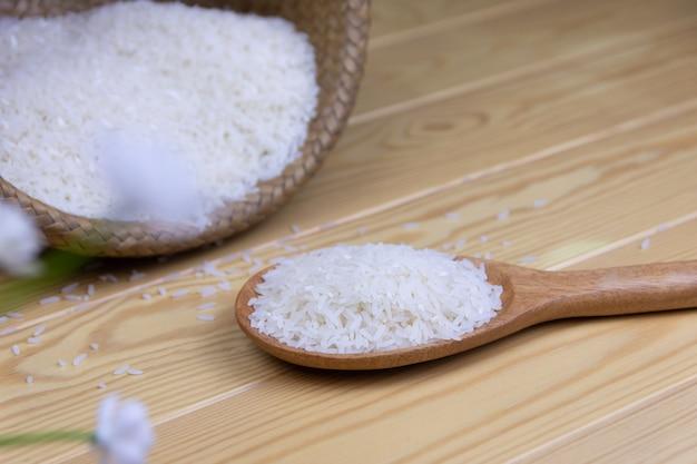 나무 국자 배경에서 쌀 나무 테이블에 컨테이너 바구니 짜기입니다.