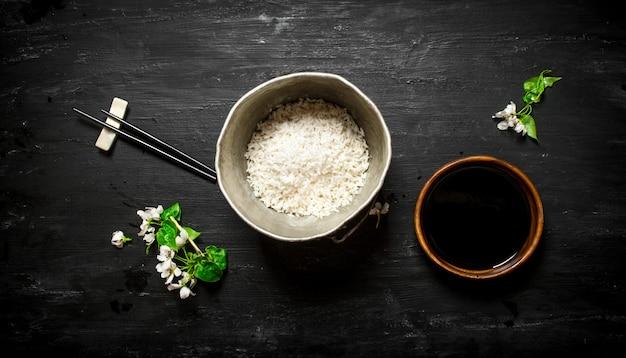 Рис в старой кастрюле и соевом соусе. на черном деревянном фоне.