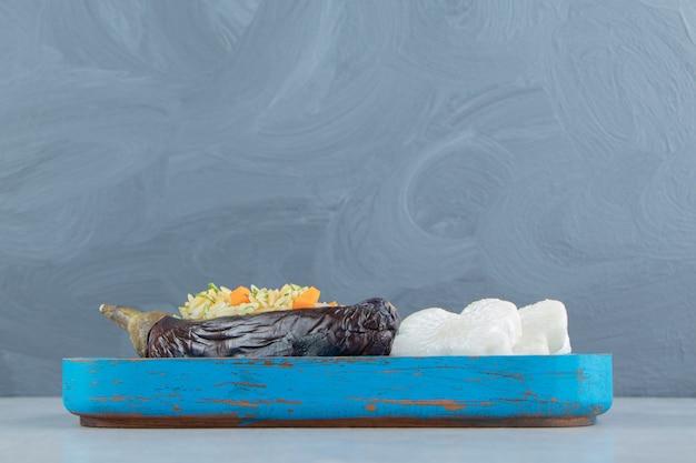 Рис в баклажанах рядом с крестообразным редисом на доске, на мраморе.