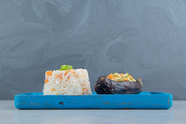 Рис в баклажанах рядом с рисом на доске, на мраморе.