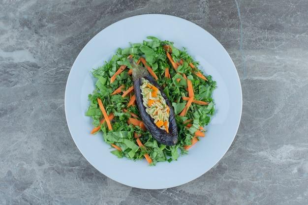 Рис в баклажанах на салатной тарелке, на мраморном столе.
