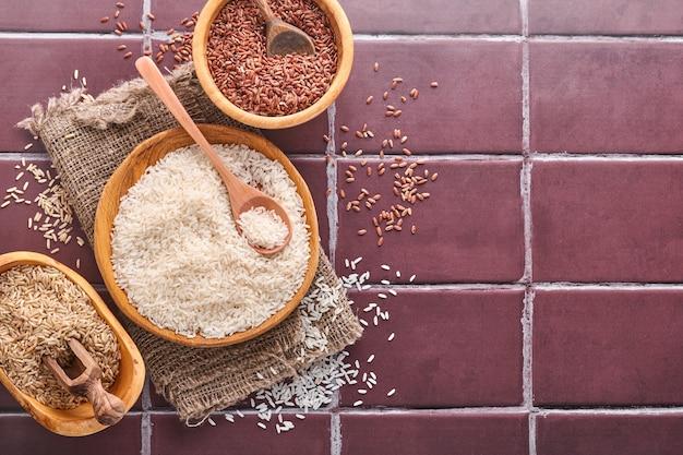 Рис, жасмин, коричневый, красный, черный в деревянной миске на коричневом каменном кухонном столе. каши без глютена. вид сверху с copyspace.