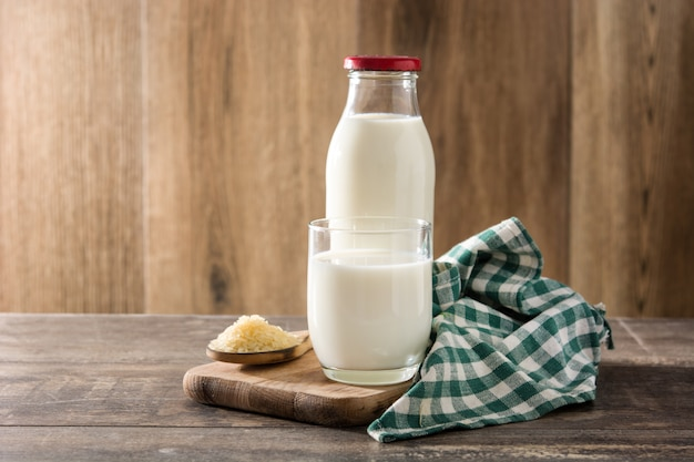 Rice milk in glass and bottle on wood table