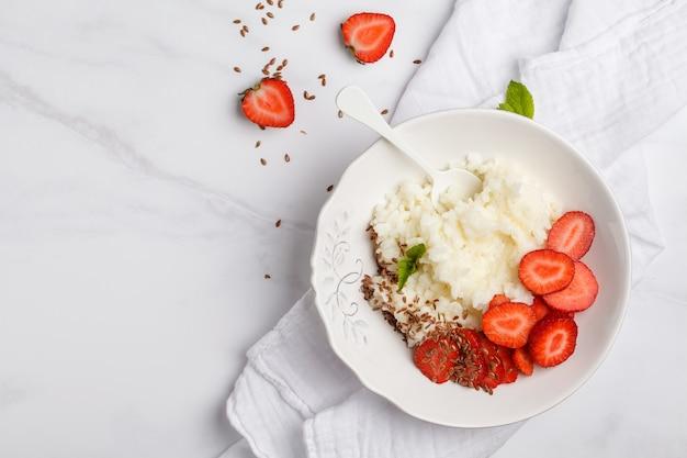 На завтрак рисовая молочная каша с клубникой и семенами льна. белая поверхность, вид сверху, копия пространства.