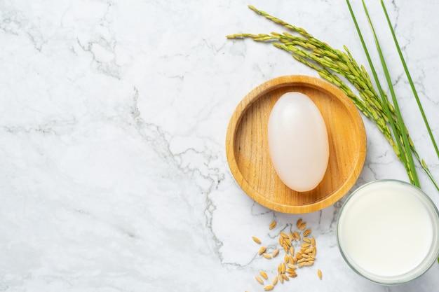 Мыло из рисового молока, стакан молока, рисовые растения и семена риса на белом мраморном полу