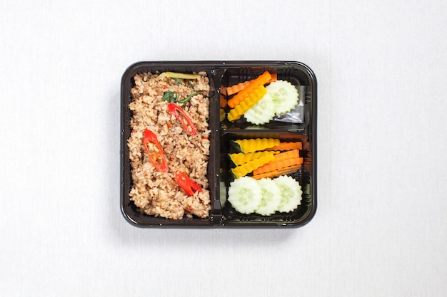 Rice mixed with basil and minced pork put in black plastic box, put on a white tablecloth, food box, thai food.