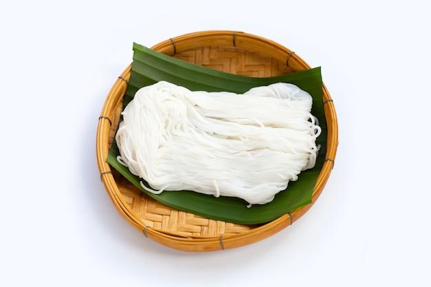Рисовая лапша в бамбуковой корзине на белом фоне.
