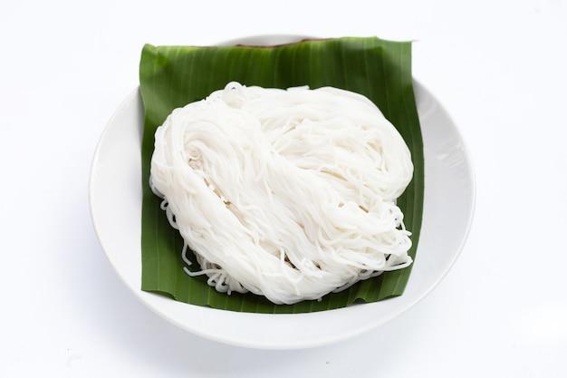 Рисовая лапша в тарелке на белом фоне.
