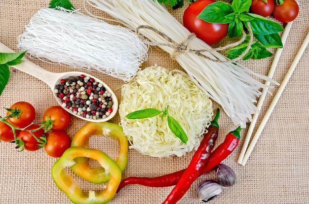 ビーフンは違います、トマト、ピーマン、箸、にんにく、バジルは袋布の上を背景に