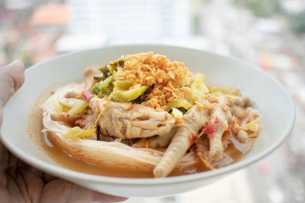 Rice noodles in fish curry sauce with chicken feet.
