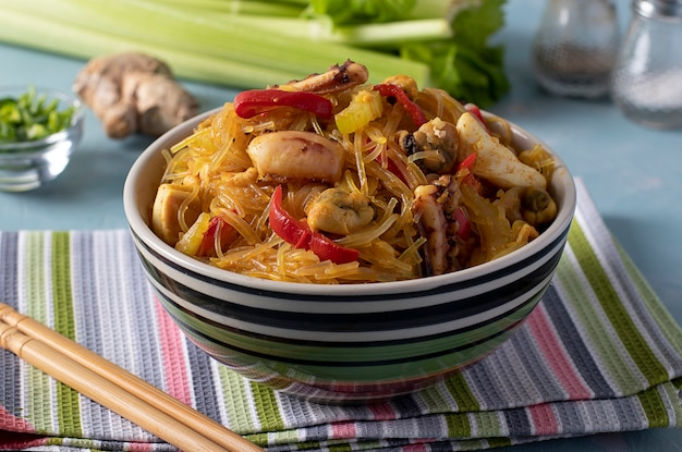 Рисовая лапша фунчоза с морепродуктами. целлофановая паста, мидии, кальмары и осьминоги, здоровая азиатская закуска в миске на голубом фоне. крупный план
