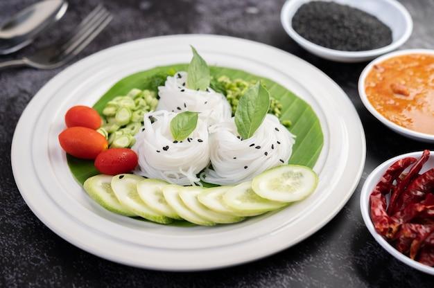 Рисовая лапша в банановом листе с красиво уложенными овощами и гарнирами. тайская еда.