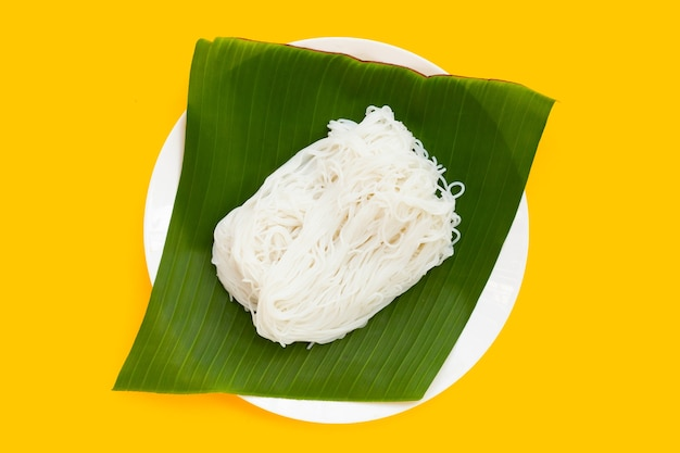 Рисовая лапша на банановом листе в белой тарелке на желтом фоне.