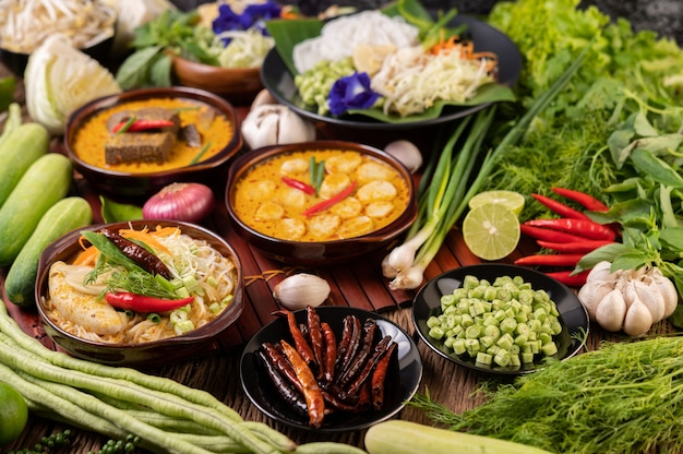 ライスヌードル、ミートボールのレッドカレー、乾燥唐辛子、バジル、キュウリ、長豆
