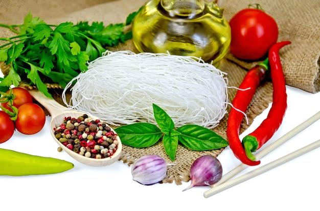 Рисовая лапша тонкая, помидоры, разные перцы, палочки для еды, чеснок, базилик, масло, мешковина, изолированные на белом фоне