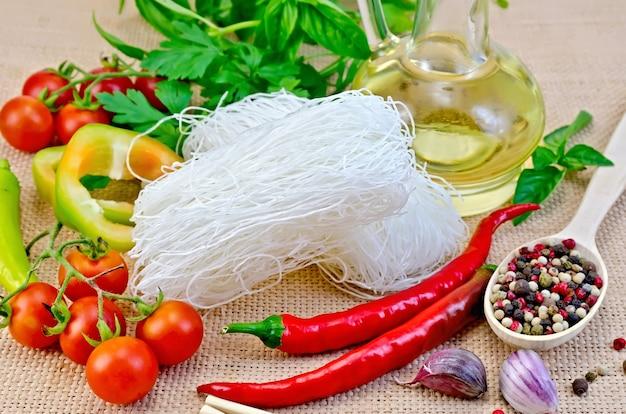薄めのビーフン、トマト、ピーマン、箸、にんにく、バジル、サッククロスの背景に植物油