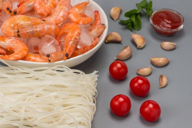 Рисовая лапша, тигровые креветки с кубиками льда в белой тарелке. помидоры, дольки чеснока, томатный соус