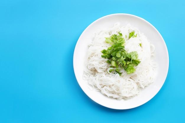 Рисовая лапша с кориандром и листьями зеленого лука в белой тарелке на синем фоне.